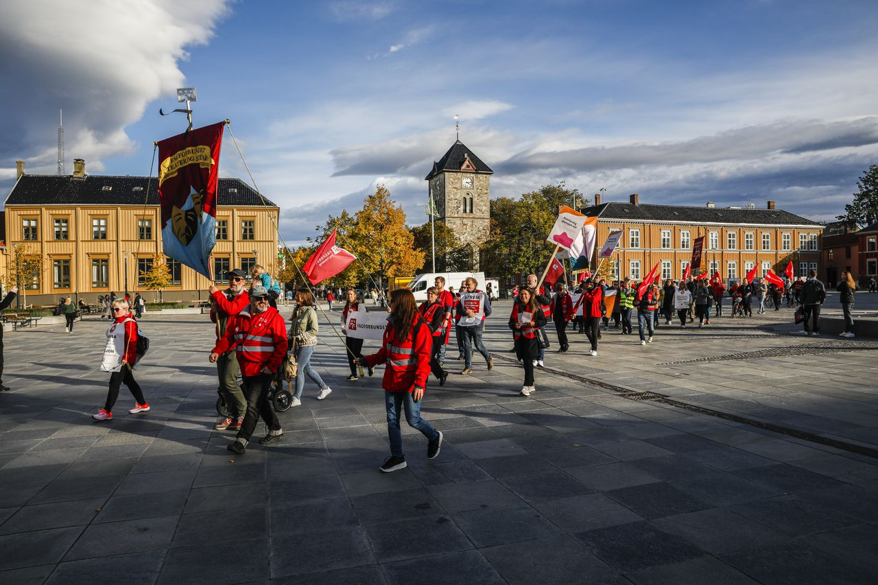 Skal det bli like fint å jobbe som å danse i sola på Torvet? Høstsola skinner på fanene til de streikende på Trøndelag Teater.  FOTO: TERJE SVAAN